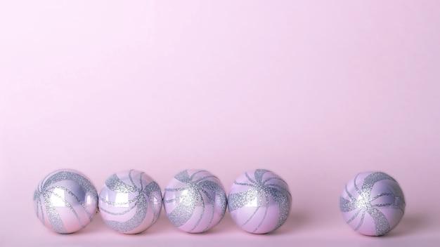 Kerst samenstelling. set roze kerstversieringen, glanzende ballen op pastel achtergrond