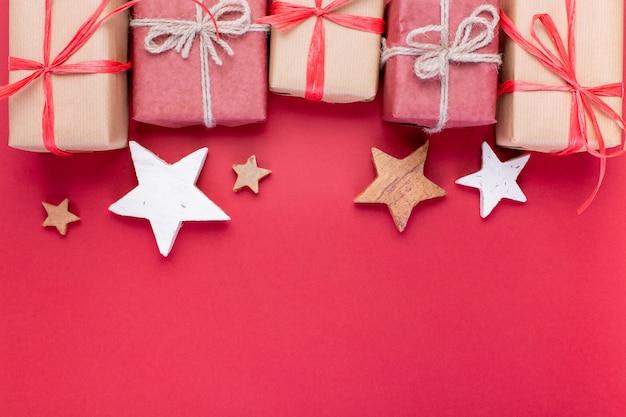 Kerst samenstelling, wenskaart. rode kerstversiering, sterren en geschenkdozen op rode achtergrond. plat lag, bovenaanzicht, ruimte voor de tekst