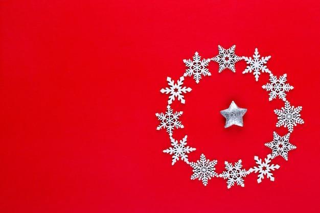 Kerst samenstelling. witte sneeuwvlokken krans decoraties op rode achtergrond. kerstmis, winter, nieuwjaarsconcept. plat leggen, bovenaanzicht, kopiëren.