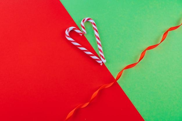 Kerst samenstelling. xmas candy canes, rode feestelijke decoraties op rode en groene achtergrond. kopieer ruimte.