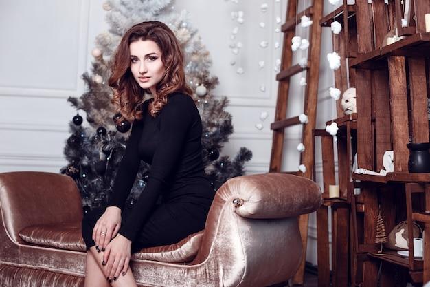 Kerst santa. mooi glimlachend vrouwenmodel. bedenken. gezond lang kapsel. elegante dame in zwarte jurk over kerstboom lichten achtergrond. gelukkig nieuwjaar