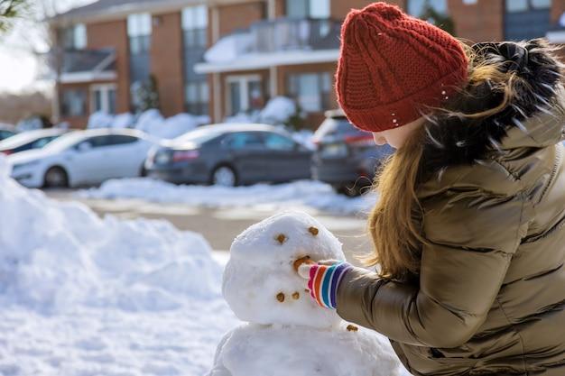 Kerst seizoen gelukkig kind beeldhouwt een sneeuwpop winter in park de sneeuw op de speelplaats