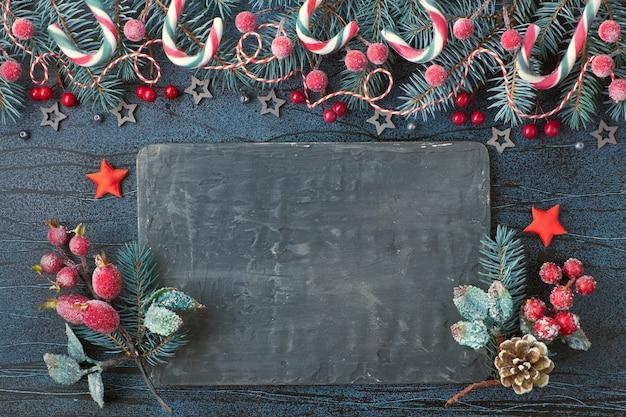 Kerst slinger met fir twijgen, rode bessen en snoep stokken op donkere, tekstruimte
