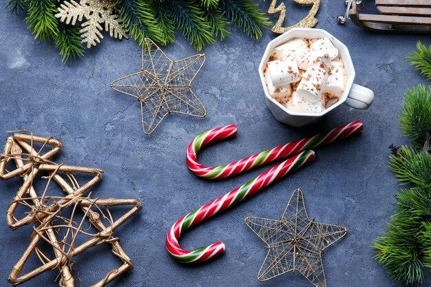 Kerst snoep stokken en kopje cacao met marshmallows op grijze achtergrond