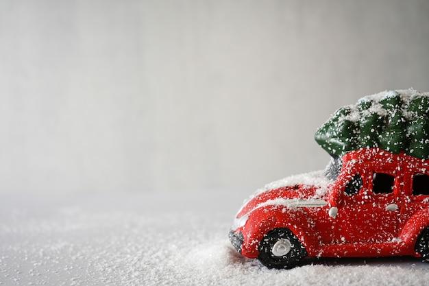Kerst speelgoed rode auto in de sneeuw op grijs. kerst samenstelling. copyspace.