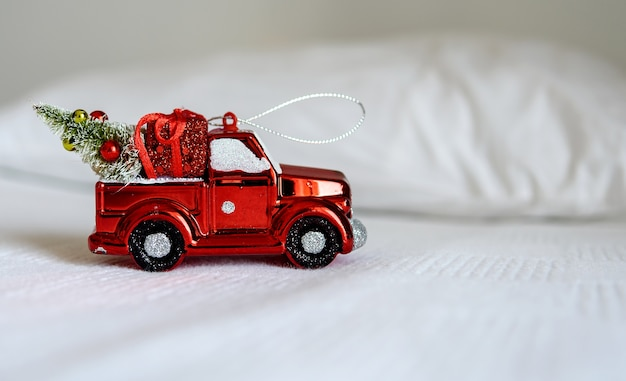 Kerst speelgoedauto op een wit bed. het concept van happy christmas, nieuwjaar, vakantie, winter, groeten.