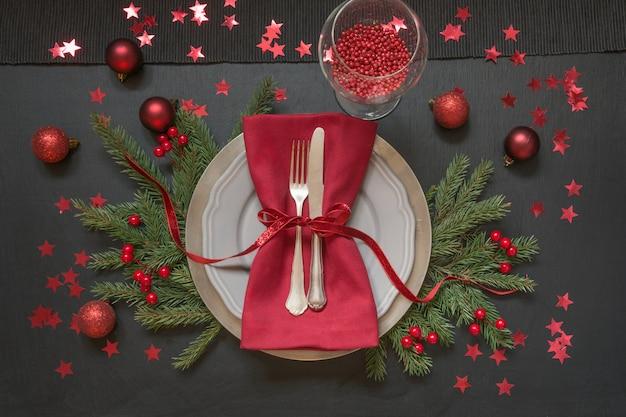 Kerst tabel instelling met rode decor op zwart.
