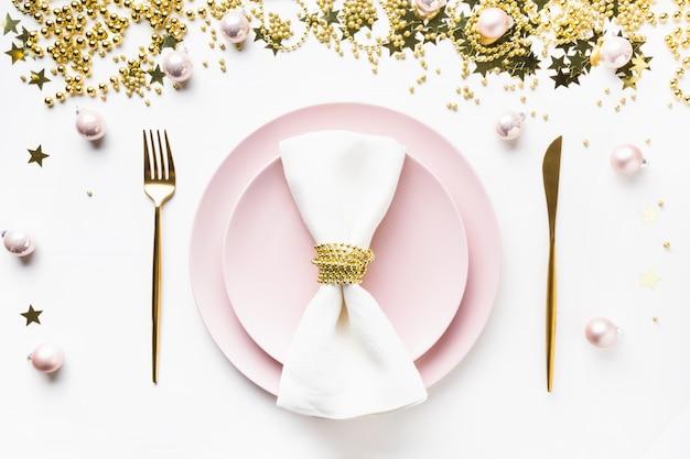 Kerst tabel instelling met roze servies, gouden zilverwerk op wit