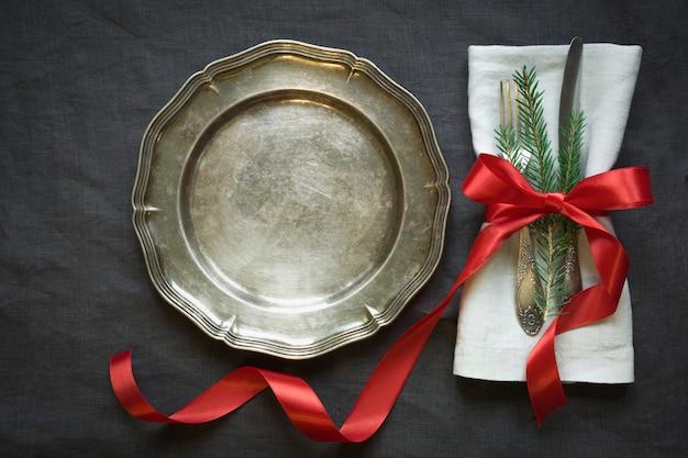 Kerst tabel instelling met vintage servies, bestek en decoraties op grijs linnen tafellaken.