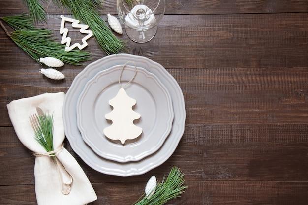 Kerst tabel instelling met witte houten decor, zilverwerk en decoraties op een houten bord.