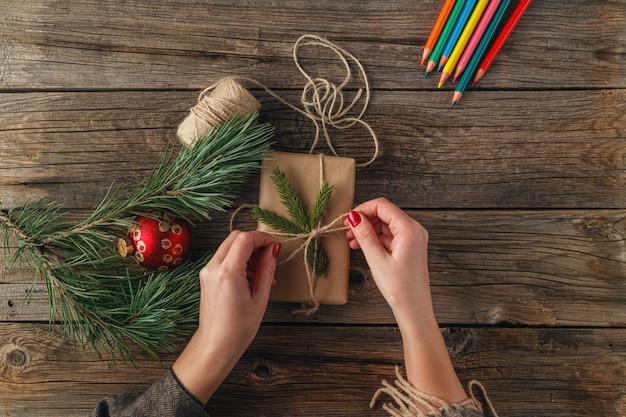 Kerst tafel. bovenaanzicht van vrouwelijke handen met cadeau of aanwezig. verpakte geschenken en rollen, vuren takken en gereedschap op armoedige houten tafel. werkplaats voor het voorbereiden van handgemaakte decoraties.
