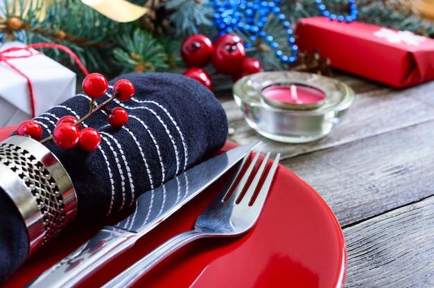 Kerst tafel instelling. rode plaat, vork, mes, kaars, servet, geschenken tak van een kerstboom op een houten achtergrond. kerst xmas nieuwjaar vakantie briefkaart.
