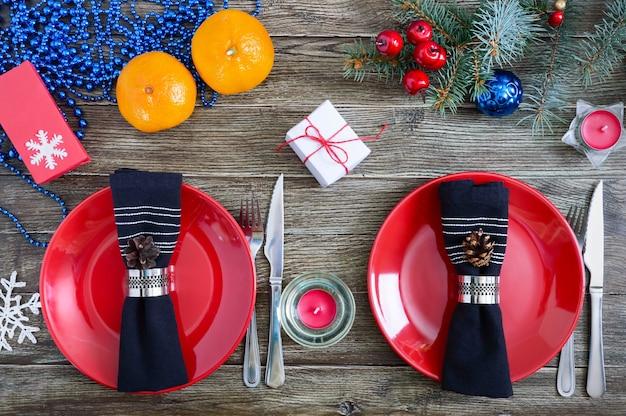 Kerst tafel instelling. rode plaat, vork, mes, mandarijnen, kaars, servet, geschenken tak van een kerstboom op een houten achtergrond. kerstmis xmas nieuwjaar vakantie achtergrond.