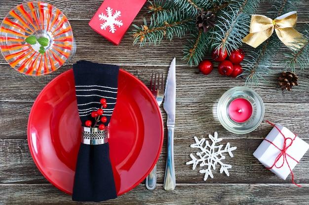 Kerst tafel instelling. rode plaat, vork, mes, martini glas, kaars, servet, geschenken tak van een kerstboom op een donkere houten achtergrond. ruimte kopiëren. kerstmis xmas nieuwjaar vakantie achtergrond.