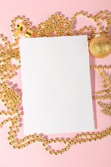 Kerst uitnodigingskaart met gouden feestelijke decoratie op roze. plat leggen