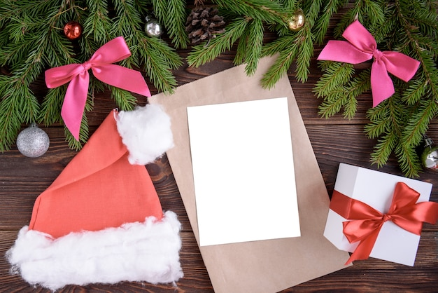 Kerst vakantie achtergrond. geschenken met een rood lint, kerstmuts en decor onder een kerstboom op een houten bord. detailopname. kopieer ruimte op bord.