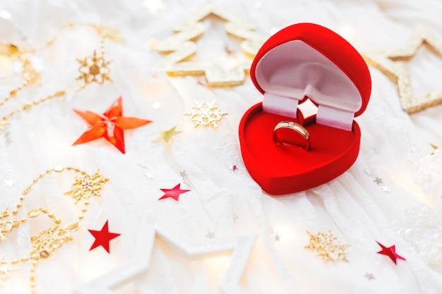 Kerst vakantie achtergrond met decoraties en verlovingsring in geschenk hart vak.