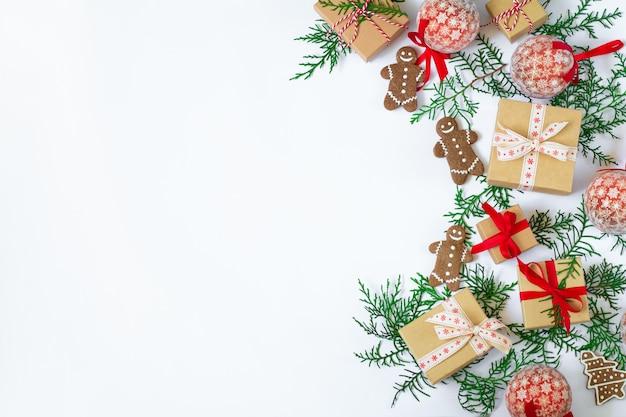 Kerst vakantie achtergrond met geschenkdozen, peperkoek, spar takken en decoraties op witte tafel. plat lag en kopieer ruimte bovenaanzicht