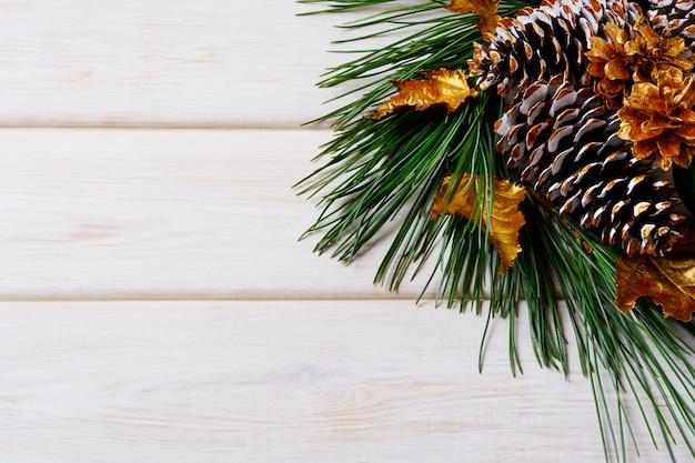 Kerst vakantie achtergrond met gouden versierde sparren en dennenappels