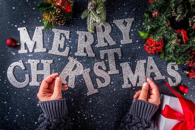 Kerst vakantie kaart achtergrond. kerstmuts met kerst- en nieuwjaarsdecor, platte lei op een donkerblauwe achtergrond, bovenaanzicht