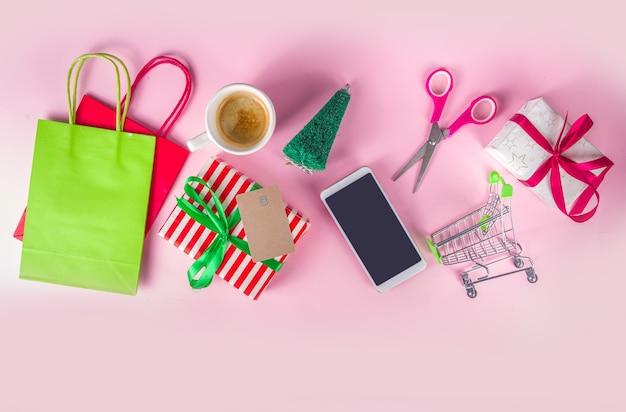Kerst verkoop zwarte vrijdag achtergrond meisje handen met symbolen nieuwjaar verkoop - boodschappentassen, geschenkdozen, winkelwagen, bankkaart, smartphone, roze kleurrijke achtergrond bovenaanzicht