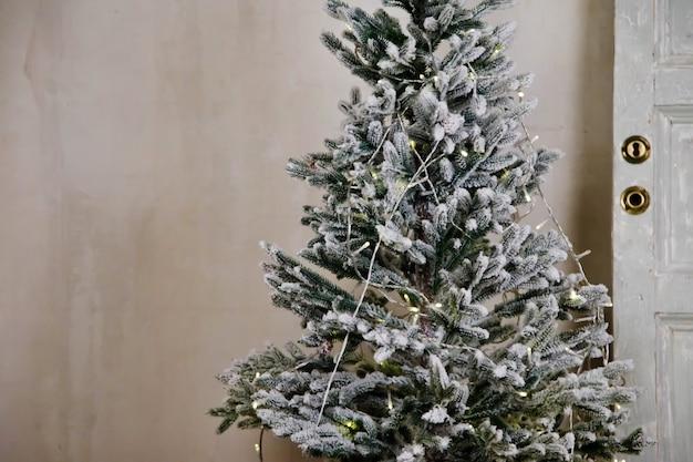 Kerst versierde boom bij de deur op lichte textuur achtergrond. kerstboom met kerstballen en speelgoed. gelukkig nieuwjaar. decor of in gezellig interieur. detailopname. ruimte kopiëren