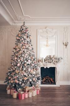 Kerst versierde boom in zachte roze kleuren met huidige dozen in klassiek interieur