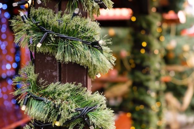 Kerst versierde stadsbeurs van verlichting led-slinger en nieuwjaarsboomtak op winterdag