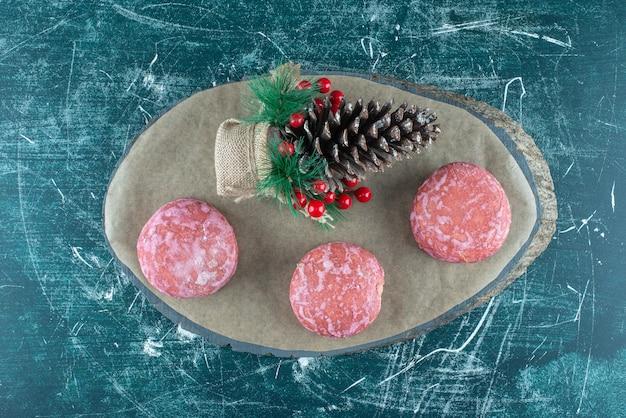 Kerst versiering en koekjes op een bord op blauw.