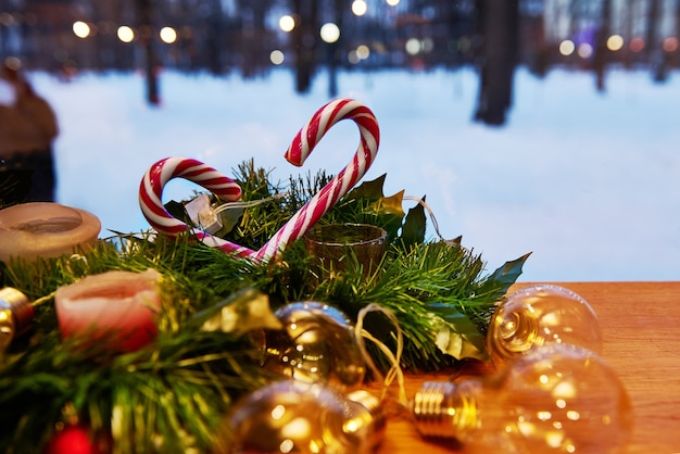 Kerst versiering. ornament op een kerstboom met zuurstokken en kaarsen met lampjes op een besneeuwde achtergrond. uitzicht vanuit het raam.