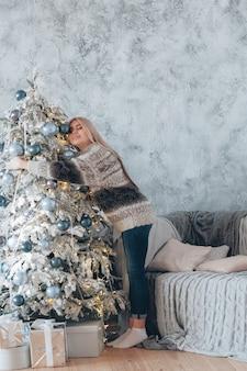 Kerst viering. dame in trui genieten van wintervakantie, versierde dennenboom knuffelen