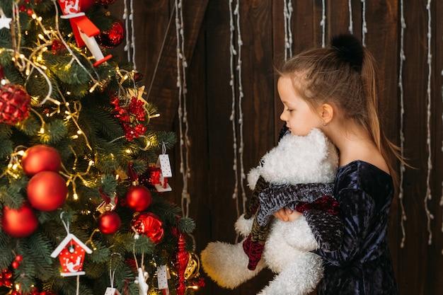 Kerst viering. zijaanzicht van schattig klein meisje permanent met teddybeer op versierde dennenboom, wachtend op wonder.