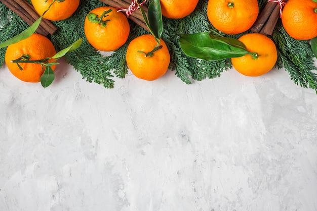 Kerst voedsel achtergrond gemaakt van mandarijnen, fir tree takken en kaneel op concrete achtergrond. bovenaanzicht. plat leggen met kopie ruimte