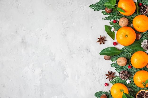 Kerst voedsel achtergrond gemaakt van mandarijnen, fir tree takken, noten, bessen en kaneel op concrete achtergrond. bovenaanzicht. plat leggen met kopie ruimte