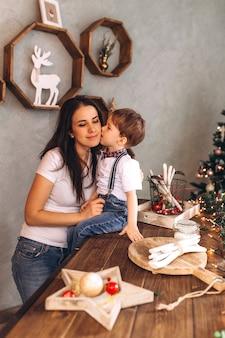 Kerst vrolijk portret van gelukkige moeder en zoon met nieuwjaar presenteert en kerstavond met viering decoratie en kerstverlichting