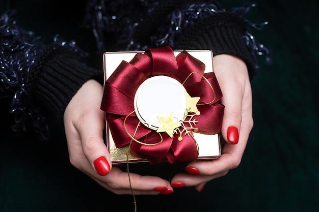 Kerst vrouw hand is een cadeau, met mooie rode geschenkdoos met kopie ruimte, close-up foto op donkere achtergrond.