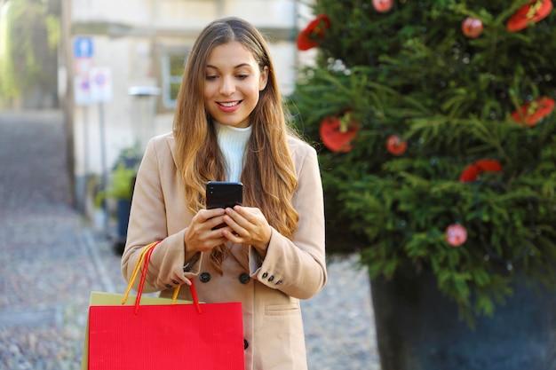 Kerst vrouw online kopen op de slimme telefoon in de straat.