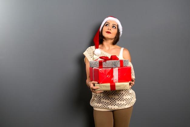 Kerst vrouw opzoeken lege kopie ruimte houden geschenkdoos aanwezig, jonge gelukkige glimlach vrouw draagt kerstman hoed, aantrekkelijk nieuwjaarsfeest meisje,