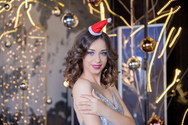 Kerst vrouw. schoonheids modelmeisje die in santa claus-hoed met rode lippen en manicure aan camera met een verraste uitdrukking kijken. close-up portret. emoties. genieten van nieuwjaarsuitverkoop, wintervakantie