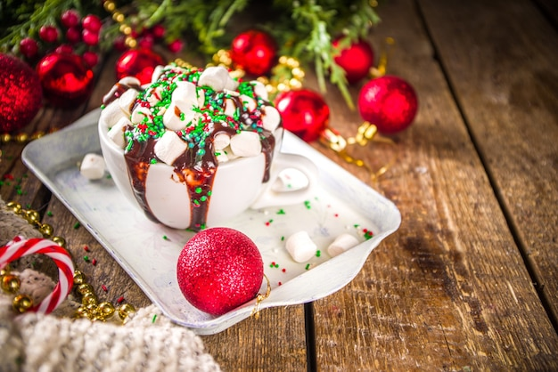 Kerst warme chocolademelk. gekke, shake-stijl warme chocolademelkbeker met veel marshmallow, chocolademotjes en groen-rode suikerstrooi