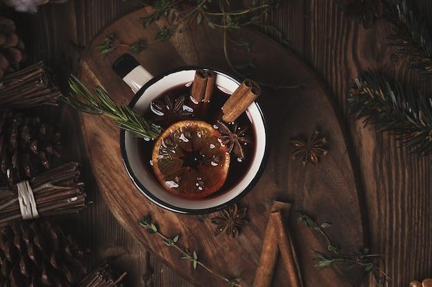 Kerst warme drank glühwein op houten tafel met kaneel, kruidnagel, specerijen.