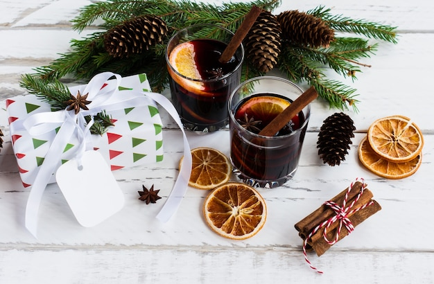 Kerst warme glühwein met kaneel kardemon en anijs op witte houten achtergrond, nieuwjaar wenskaart