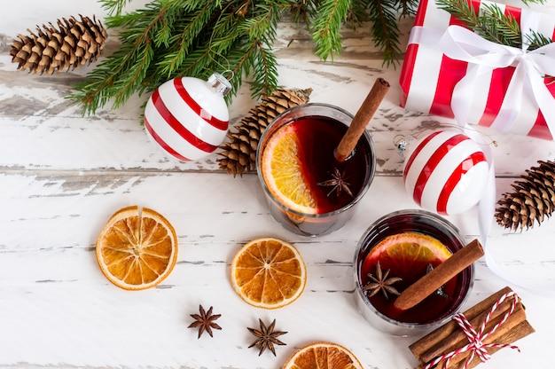 Kerst warme glühwein met kaneel kardemon en anijs op witte houten achtergrond, nieuwjaar wenskaart.
