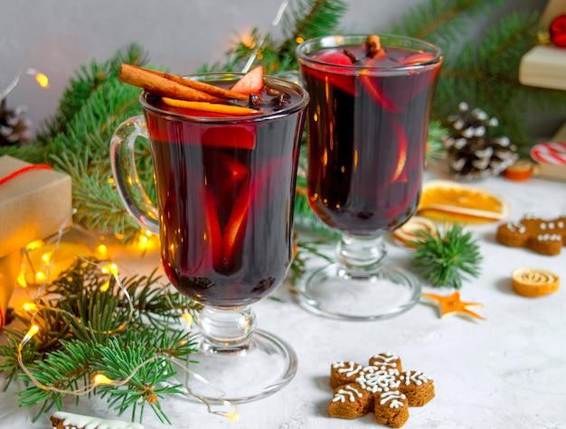 Kerst warme rode wijn met kruiden en sinaasappels op een rustieke houten tafel.nieuwjaar traditionele dranken.