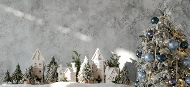 Kerst wenskaart. feestelijk interieur. winter miniatuur dorp display, dennenboom bedekt met sneeuw.