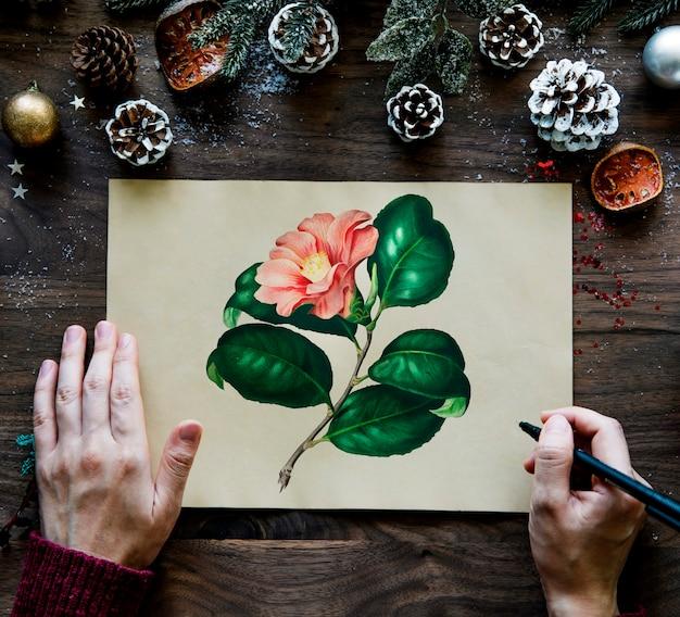 Kerst wenskaart met dennenappels en tekening van bloem