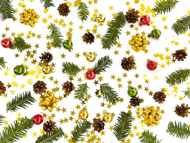 Kerst wenskaart. verspreide fir tree takken, kerstballen, sterren, kegels en strikken. eenvoudige wintervakantie plat.