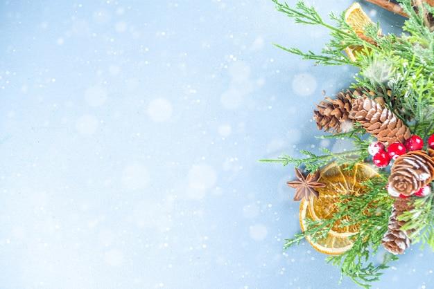 Kerst winter lichtblauw witte achtergrond, met dennenboom sparren takken, dennenappels, gedroogde sinaasappel, kruiden, ingrediënten voor wintercocktails, decoraties, flatlay bovenaanzicht kopieerruimte
