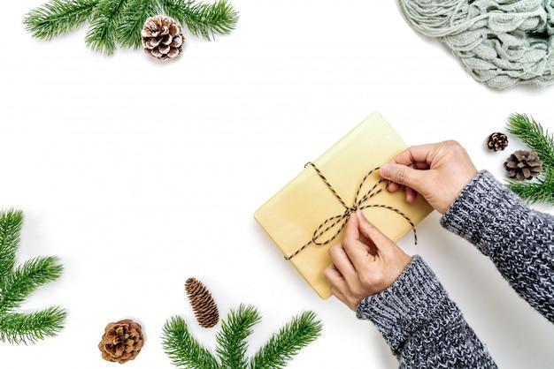 Kerst winter samenstelling. de vrouw overhandigt de verpakkende doos van kerstmisgiften met denneappels, spartakken op witte achtergrond. plat lag, bovenaanzicht, kopie ruimte