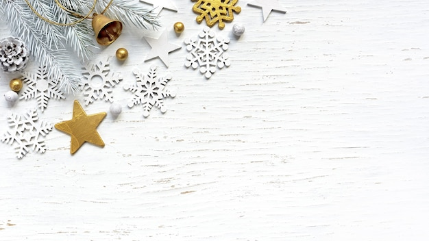 Kerst witte fir tree takken dennenappel oude gouden jingle bell en witte versieringen op witte houten achtergrond.